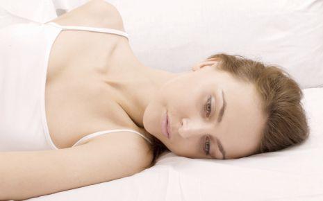 Eine nachdenklich aussehende Frau liegt im Bett.