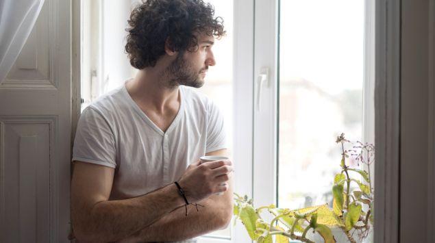 Ein Mann blickt nachdenklich aus dem Fenster.