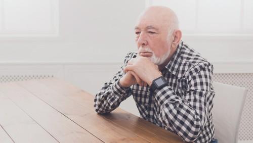 Ein älterer Mann sitzt nachdenklich an einem Tisch.