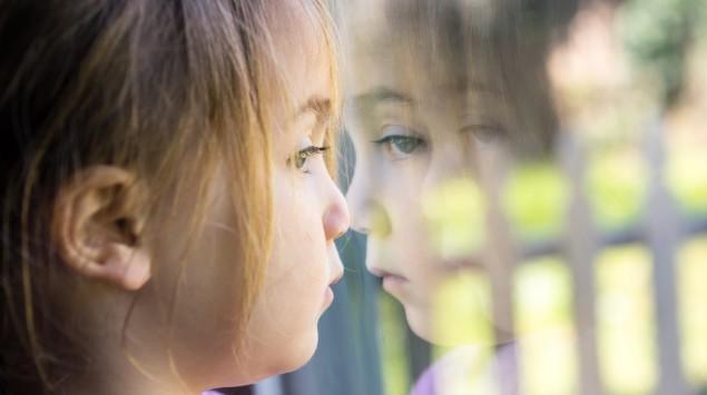 Ein kleines Mädchen blickt nachdenklich aus dem Fenster.