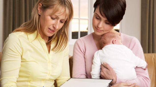 Nachsorgehebamme bei junger Mutter und Säugling zu Hause.