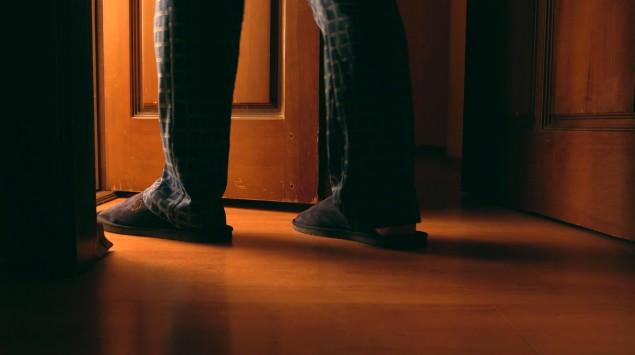 Ein Mann in Schlafanzug udn Pantoffeln tritt aus einem dunklen Zimmer in einen erleuchteten Raum.