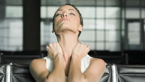 Eine Frau sitzt am Schreibtisch und dehnt ihren Nacken.