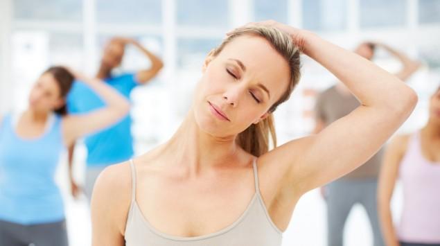 Eine Gruppe Erwachsener führt Übungen zur Dehnung der Nackenmuskulatur aus.