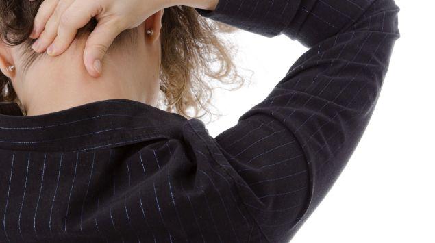 Das Bild zeigt eine Frau, die ihren Nacken massiert.