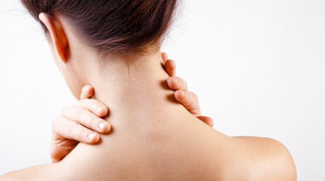 Rückenansicht einer Frau, die sich an den Nacken fasst.
