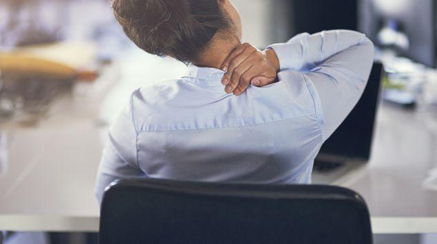 Das Bild zeigt einen Büroangestellten mit Nackenschmerzen, die in seinem Bürostuhl sitzt.