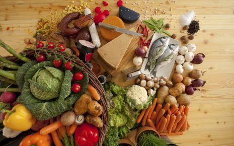 Diabetes Tipps für die Ernährung: Auf einem Tisch liegt eine große Auswahl unterschiedlicher unzubereiteter Lebensmittel.