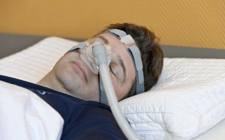 Ein schlafender Mann mit Beatmungsmaske in Form einer Nasenmaske.