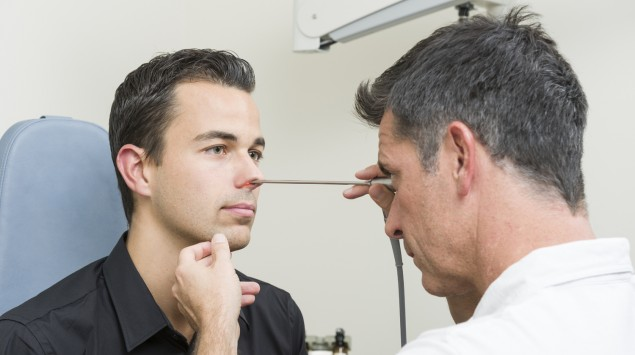 Ein Arzt untersucht die Nase eines Mannes mit einem Rhinoskop
