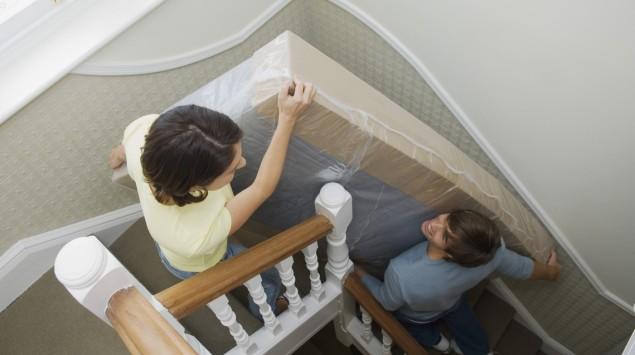 Ein junges Paar trägt eine in Folie und Karton verpackte Matratze eine enge Treppe hinauf.