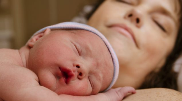 Neugeborenes und Mutter schlafen.