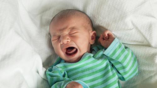 Ein Neugeborenes in grün getreiftem Oberteil weint.