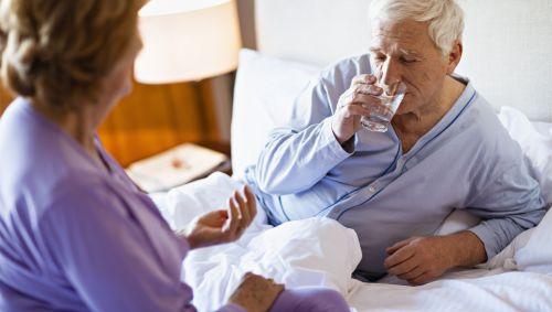 Ein Mann liegt krank im Bett und trinkt Wasser.