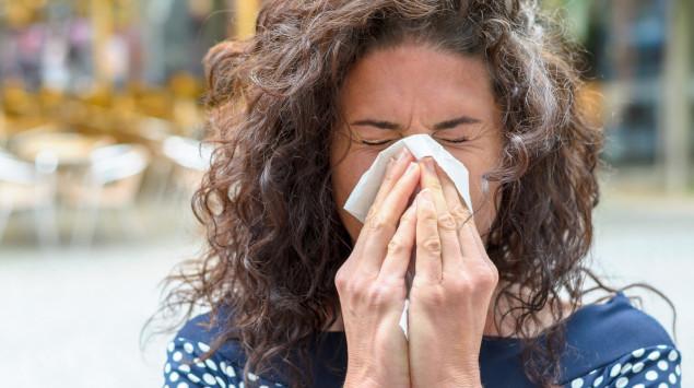 Eine Allergikerin niest in ein Taschentuch. Wie sich die Symptome bei Covid-19 und einer Allergie unterscheiden.