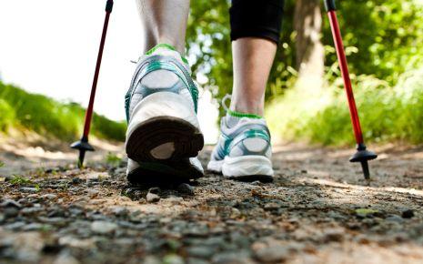 Arthrose: Man sieht die Füße einer Frau beim Nordic Walking.