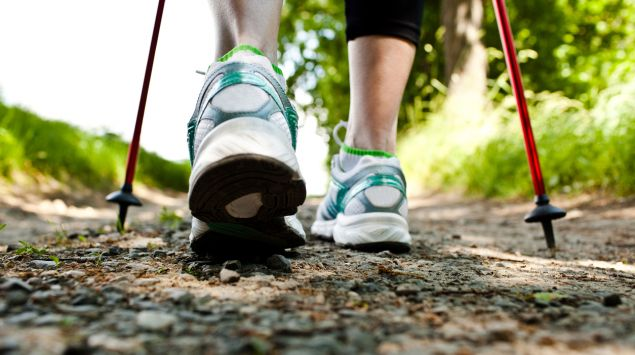 Man sieht die Füße einer Frau beim Nordic Walking.