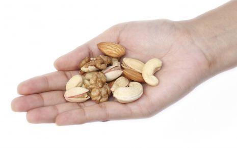 Nüsse sind gesund: Jemand hält verschiedene Nüsse in der Hand.
