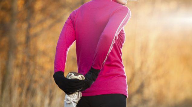 Man sieht eine Frau in Joggingoutfit, die ihren Oberschenkel deht.
