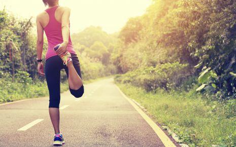 Eine Joggerin dehnt ihren Oberschenkel. Ein Aufwärmprogramm vor dem Sport ist wichtig, um einem Muskelfaserriss vorzubeugen.