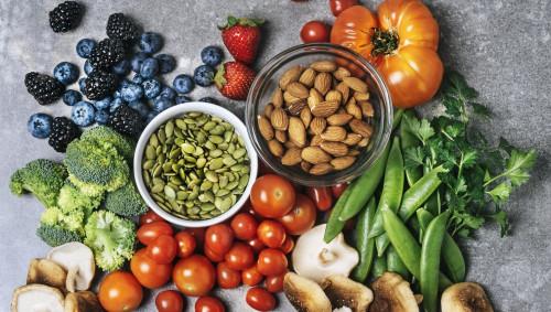 AUf einem Tisch liegen frisches Obst und Gemüse neben zwei Schalen mit Kürbiskernen und Mandeln.