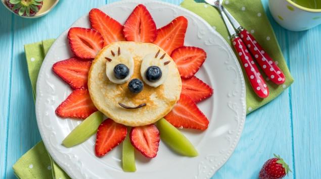 Ein Sonnen-Gesicht aus Obst und einem kleinen Pfannkuchen