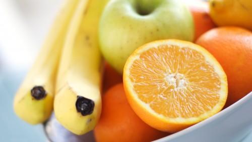 Man sieht eine Schale mit Orangen, Bananen, Zitronen und Äpfeln.