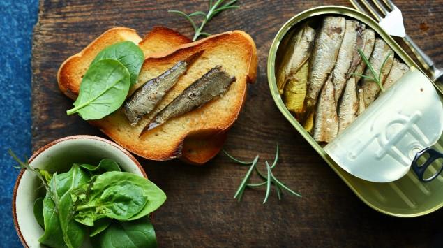 Ölsardinen in Dose und auf Brot liegen auf Holzbrett