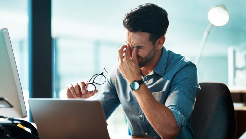 Ein junger Mann sitzt an einem Computerarbeitsplatz und reibt sich die Augen.