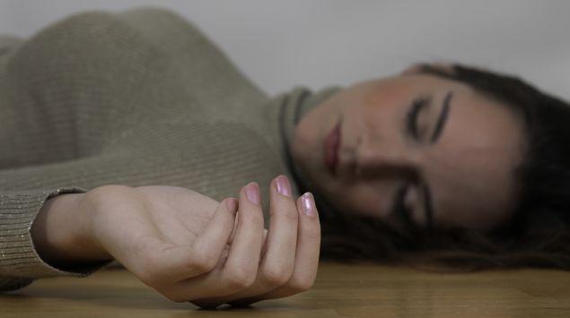 Das Bild zeigt eine Frau, die ohnmächtig am Boden liegt.