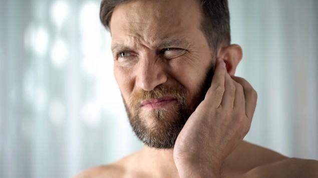 Wasser im Ohr: Ein Mann fasst sich ans Ohr und verzieht das Gesicht.
