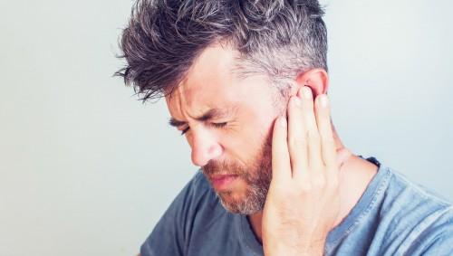Ein Mann hält sein schmerzendes Ohr.