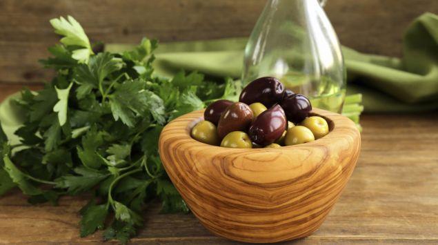 Man sieht ein Holzschälchen mit grünen und schwarzen Oliven.