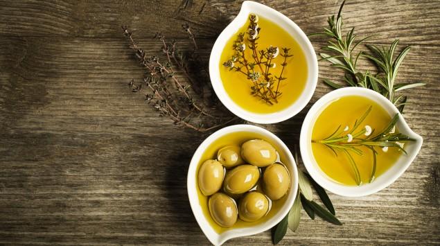 Das Bild zeigt Oliven und Olivenöl.