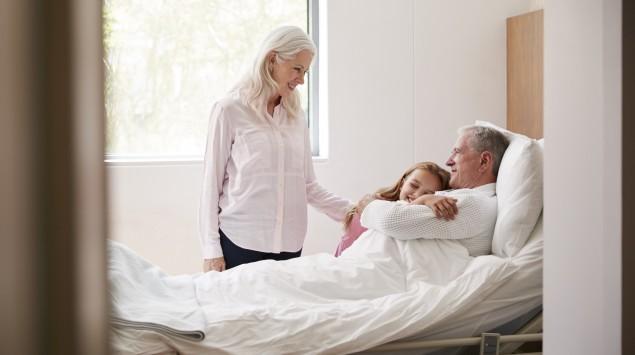 Enkelin umarmt ihren Großvater im Krankenhaus.
