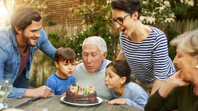 Familie feiert mit Torte Opas Geburtstag
