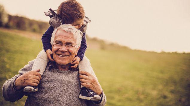 Das Bild zeigt einen älteren Mann mit seinem Enkel auf den Schultern.