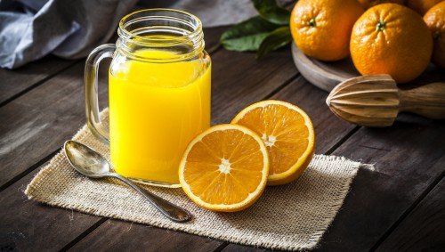 Ein Glas Orangensaft mit zwei Orangenhälften