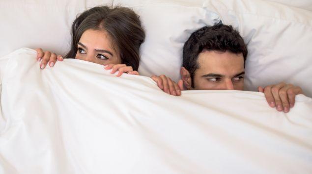 Ein junges Paar schaut verstohlen unter der Bettdecke hervor.