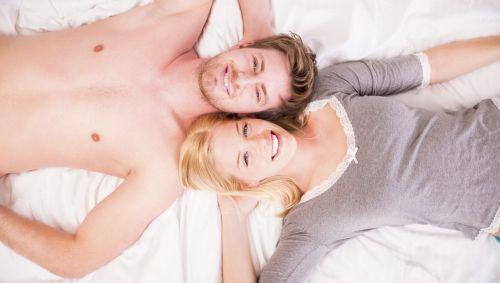 Mann und Frau liegen lächelnd im Bett.