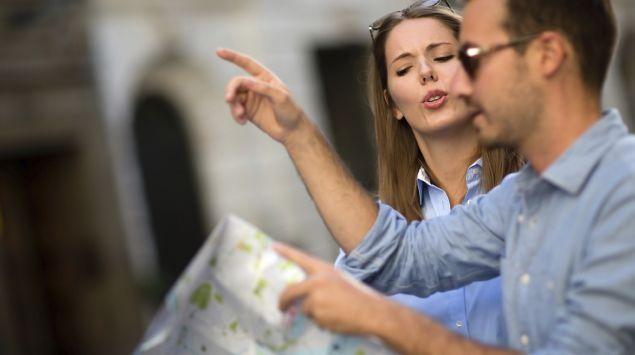 Ein Paar mit einer Reisekarte in der Hand diskutiert über den richtigen Weg.