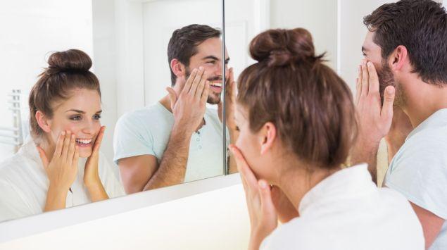 Ein paar cremt sich morgens vor dem Spiegel ein.