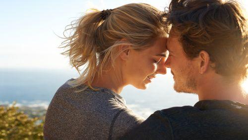 Ein junges Paar steht Stirn an Stirn auf einer Anhöhe über dem Meer.