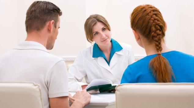 Man sieht ein junges Paar bei einem Arzttermin.