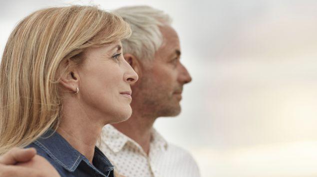 Ein älteres Paar steht Arm in Arm nebeneinander und guckt in die Ferne.