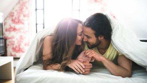 Eine Frau und ein Mann liegen bäuchlings im Bett und schmusen miteinander.