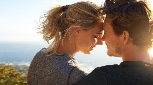 Ein junges Paar am Meer steckt die Köpfe zusammen.
