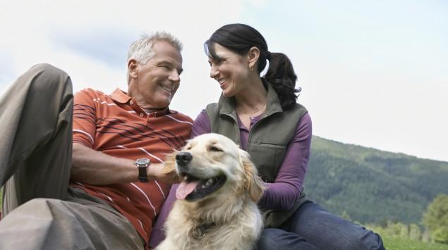 Ein älteres Paar sitzt mit einem Hund auf einer Wiese.