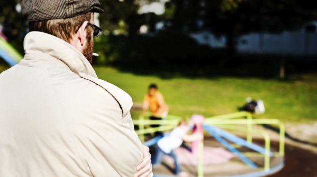 Ein Mann beobachtet Kinder auf dem Spielplatz.