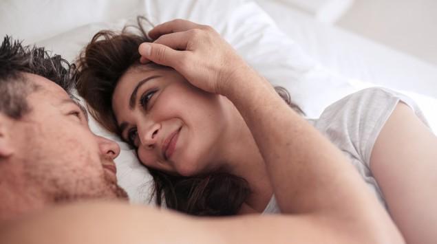Man sieht einen Mann und eine Fau im Bett.